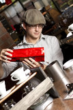 Barista pours coffee beans into container. A cafe employee pours fresh coffee beans into grinder. focus on beans Royalty Free Stock Photo