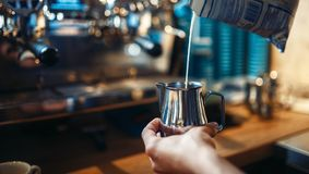 Barista pours cream into the cup of coffee. Barista in apron pours cream into the cup of coffee, cafe counter on background. Professional cappuccino preparation Royalty Free Stock Photos