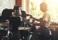 Barista prepares cappuccino in his coffee shop stock images