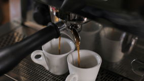 Barista prepares two cups of espresso. Close up stock footage