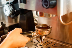 Barista preparing coffee in a cafe. Royalty Free Stock Image
