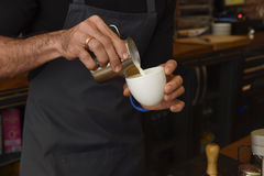 Barista preparing coffee cream pouring milk in mug decorating with foam Stock Photography