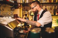 Barista preparing coffee in espresso machine. Handsome barista preparing cup of coffee in espresso machine behind bar counter Royalty Free Stock Photos