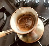 Barista preparing hot tasty drink from copper turk stock photography