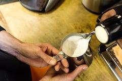 Barista preparing milk for takeaway coffee. Royalty Free Stock Image