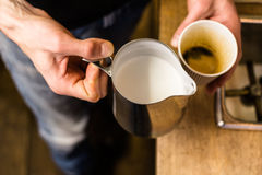 Barista preparing to add milk for takeaway coffee. Stock Photography