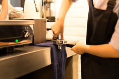 Barista presses ground coffee using tamper. In cafe Royalty Free Stock Photo