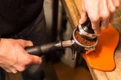 Barista presses ground coffee using tamper. Royalty Free Stock Photo