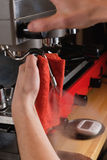 Barista produces steam from the coffee machine. Barista produces hot steam from the coffee machine with a red towel in his hands Royalty Free Stock Photos