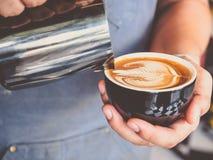 Barista professionale con la tazza di caffè che fa il bello modello di arte del latte immagini stock libere da diritti