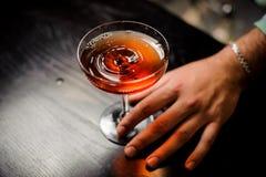 Barista professionista con il cocktail rosso in un vetro di martini Fotografie Stock Libere da Diritti
