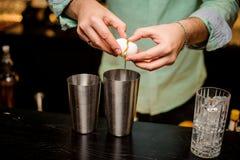 Barista professionista sul lavoro in tuorlo d'uovo di versamento della barra in vetro per la bevanda Fotografia Stock