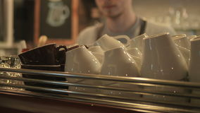 The barista put two cups on the coffee machine. Close-up. The camera is moving from left to right. The man on a blurred background is holding a cups in hands and stock footage