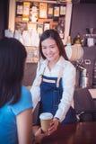 Barista que da la taza de café a su cliente y sonrisas Imágenes de archivo libres de regalías