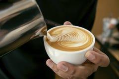 Barista que faz o latte ou a arte do cappuccino com espuma espumoso, café foto de stock royalty free
