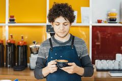 Barista que guarda o copo de café perto do contador da barra no café moderno brilhante fotografia de stock royalty free