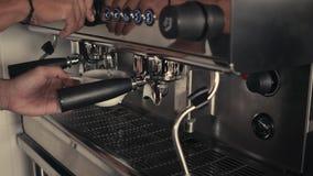 Barista que hace americano o capuchino en un vaso del acero inoxidable en una máquina de café express industrial Primer Concepto metrajes