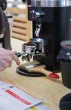 Barista que hace el café en máquina del café foto de archivo