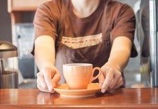 Barista que oferece a xícara de café alaranjada Fotografia de Stock Royalty Free