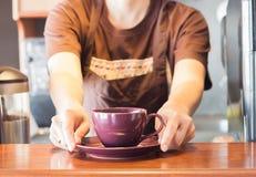 Barista que oferece a xícara de café roxa Fotografia de Stock Royalty Free
