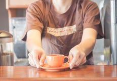Barista que ofrece la mini taza de café anaranjada Imagen de archivo libre de regalías