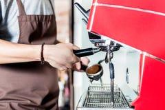 Barista que prepara el café en la máquina del portafilter en café fotos de archivo