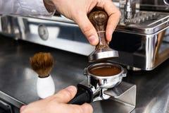Barista que pressiona o café à terra no portafilter com uma calcadeira fotos de stock royalty free