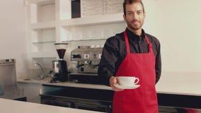 Barista que sirve una taza de café a la cámara almacen de metraje de vídeo
