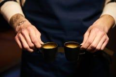 Barista räcker att rymma två lilla koppar för espresso Arkivfoto