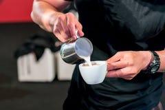 Barista ręka nalewa świeżą mleko pianę w kawy espresso filiżankę zdjęcia stock