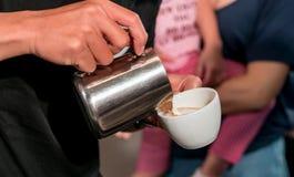 Barista ręka nalewa świeżą mleko pianę w kawy espresso filiżankę zdjęcie stock