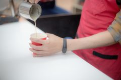 Barista in a red apron pours coffee in a plastic cup. Close up shot. Detailed royalty free stock images