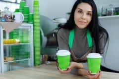 Barista in schort houdt in handen hete koffie in groene meeneemdocument kop De koffie haalt bij koffiewinkel weg stock afbeeldingen