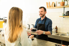 Barista serving coffee to customer Stock Image