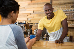 Barista serving coffee to female customer in cafe Royalty Free Stock Photo