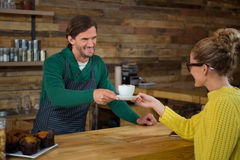 Barista serving coffee to female customer in cafe Stock Images