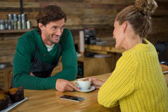 Barista serving coffee to woman in cafeteria Royalty Free Stock Image