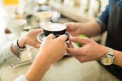 Barista serving a cup of coffee to customer. Closeup of the hands of a barista giving a cup of coffee to a customer in a coffee shop Stock Image
