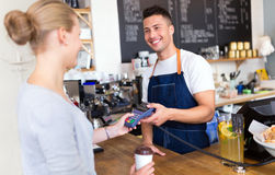 Barista serving customer in coffee shop Royalty Free Stock Photo