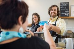 Barista Serving Customer. Happy barista serving customer cup of coffee Royalty Free Stock Image