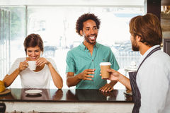 Barista serving two happy customers Stock Image