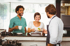 Barista serving two happy customers Stock Photos