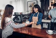 Barista sirvió la taza de café caliente al cliente con la cara de la sonrisa en el cou Foto de archivo libre de regalías