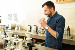 Barista smelling a cup of coffee. Profile view of an attractive male barista smelling and enjoying a cup of freshly brewed coffee in a cafe Stock Photography