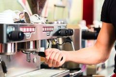 Barista som förbereder espresso på kaffebryggaren Royaltyfri Fotografi