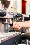 Barista som förbereder espresso på kaffebryggaren Arkivbild