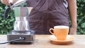 Barista som häller varmt kaffe från mokakrukan stock video