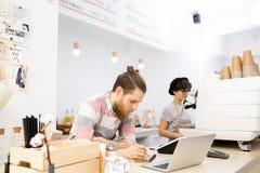 Barista som kontrollerar beställningar i notepad arkivfoton