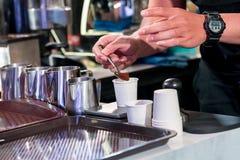 Barista som kontrollerar fint malt kaffe för att optimera molar arkivbilder