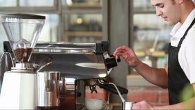 Barista sorridente che cuoce a vapore latte alla macchina del caffè video d archivio